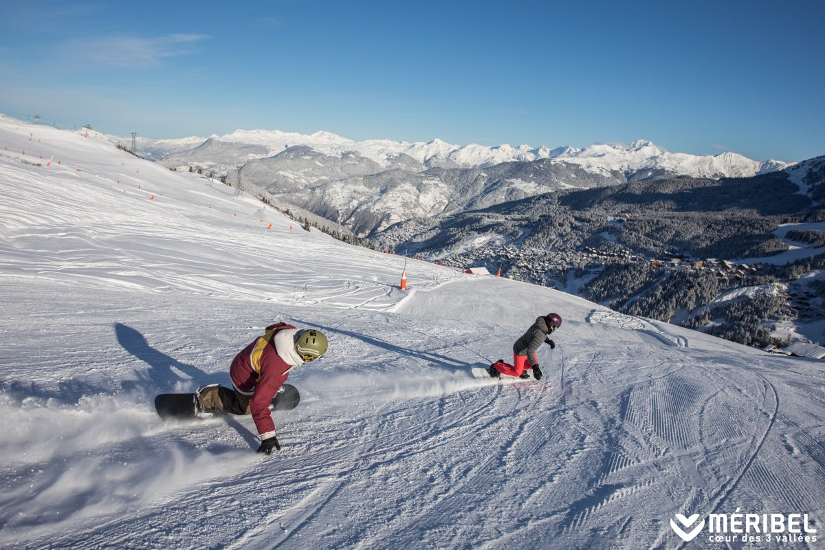Which is better, skiing or snowboarding? Two people snowboarding together in Meribel