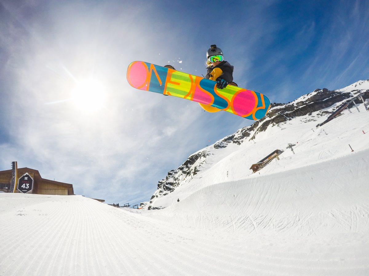 Which is better, skiing or snowboarding? Snowboarder doing a jump in the Meribel DC snowpark