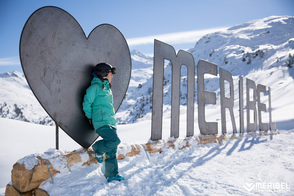 Girl standing by an 'I heart Meribel' sign in the snow