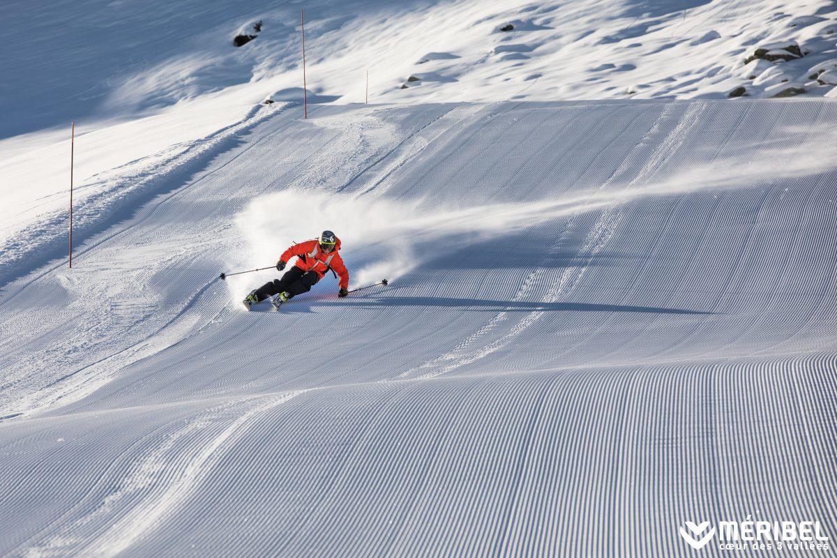 Which is better, skiing or snowboarding? Skier racing down piste in Meribel