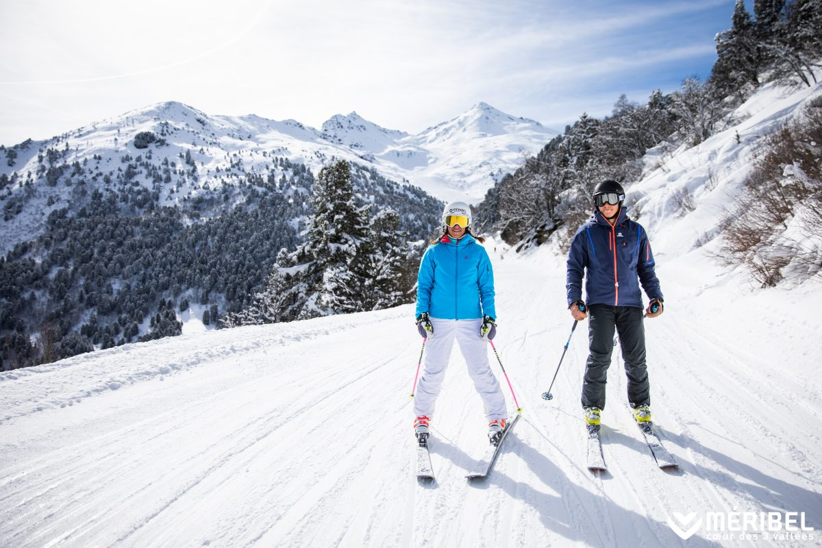 A couple skiing down a mountain with trees.