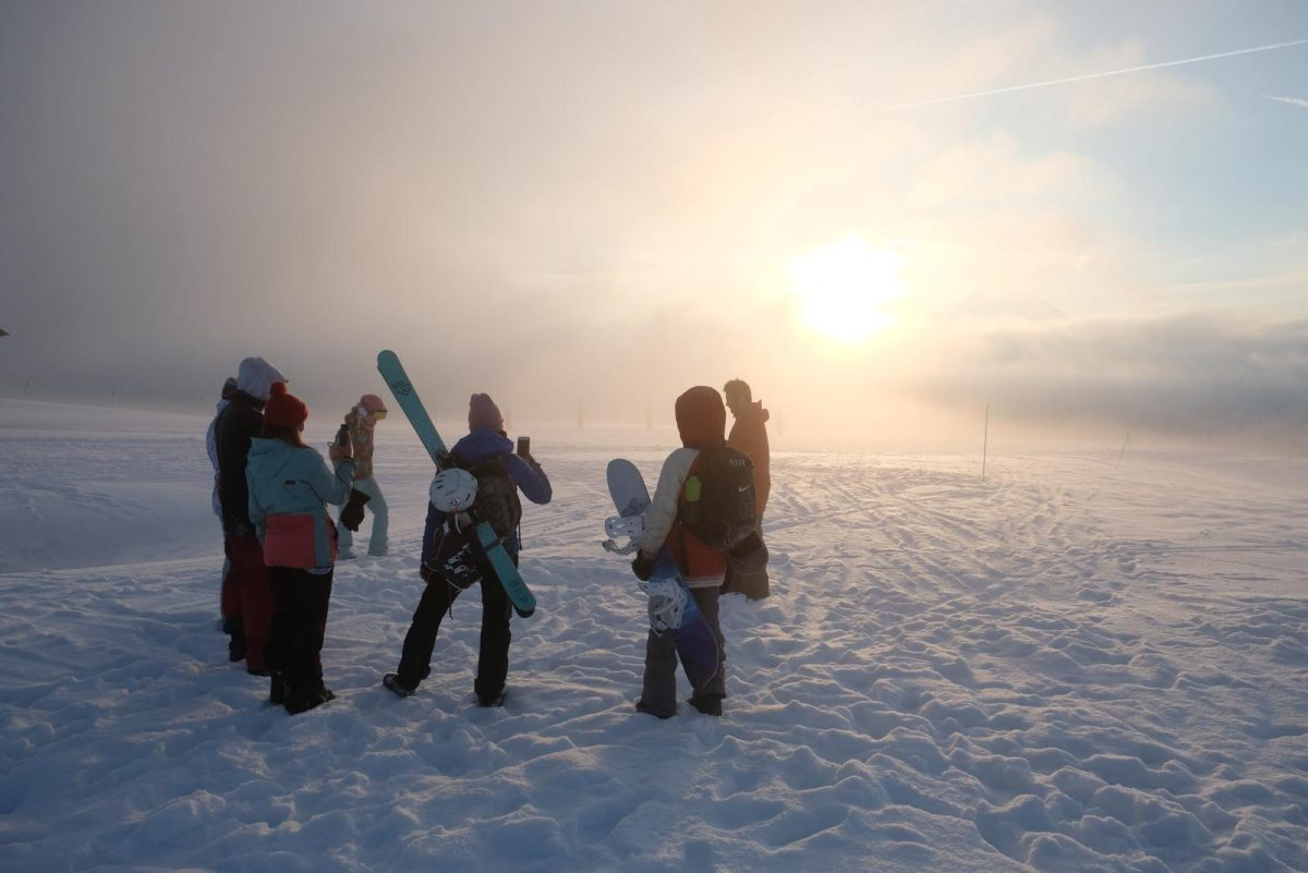 Friends in the snow with snowboards and sunset