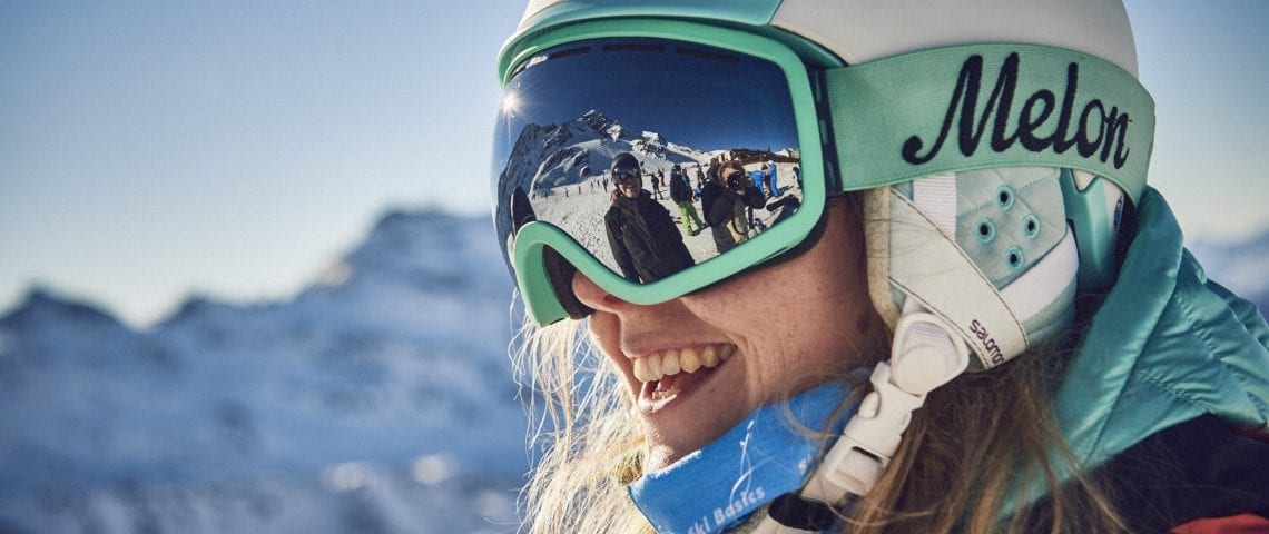 Woman skiing with helmet and reflection of friend in goggles