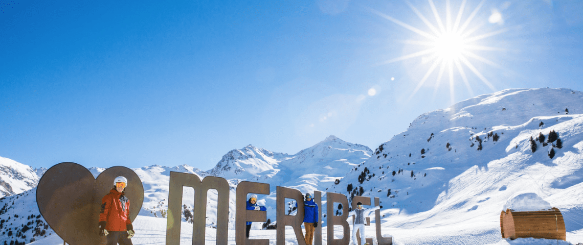 People stood in front of 'heart Meribel' sign in the snow